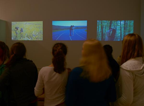 Gallery visitors viewing a 3 channel video piece by Bang Geul Han